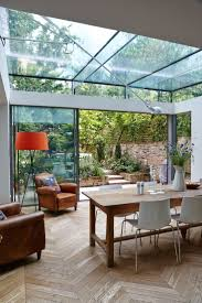 Trombe - Internal photo of a dining room extension in London. It  incorporates a structurally glazed roof supported on laminated glass