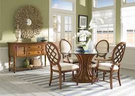 dining room table mirror top: leather padded set of four victorian dining room chairs with wood frames and a round glass dining table in a dining room with a wood drawer and mirror