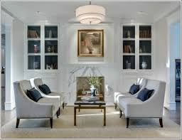 simple minimalis living room decorating ideas white painted walls neutral colored armchairs glass pocket bookcase doors neutral area rug simple hinged lamp