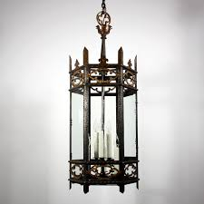 two matching large antique gothic revival iron and bronze lanterns circa 1910 with clear glass panels each chandelier begins with a cast bronze