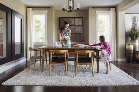 mother and daughter setting table in dining room