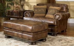 beautiful first grade leather chair and a half with ottoman in brown color with peach cushion