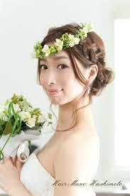 ルーズな編み込みと低めにまとめたヘアアレンジグリーンと小花の花かん