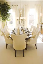 bright sunny dining room with oval wood table and eight plush cream colored dining chairs