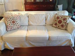 cozy couch design with white shabby chic slipcovers and decorative cushions for traditional family room design