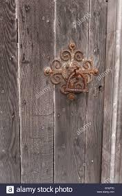 rusty old fashioned door mechanism handle on weathered oak door from meval street