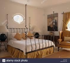 Ovale Fenster über Moderne Schwarze Schmiedeeisen Bett Mit Weißen