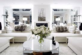 white sofas and circular coffee table in mirrored living room of london home uk