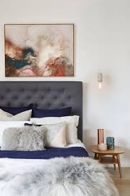 Grey upholstered bed with moody artwork hanging above. The dark blue and  grey bedding is