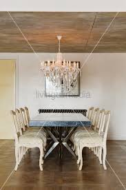 table and vintage style pale chairs below chandelier hanging from exposed concrete ceiling