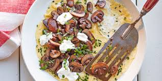 a basil omelette in a pan topped with mushrooms