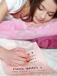 girl lies on a bed and writes the love letter Stock Photo. girl lies on a bed and writes the love letter - girl-lies-bed-writes-love-letter-17752520