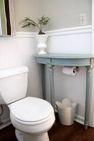 a small end table placed above a toilet paper roll is a cool bathroom storage