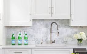 white tile backsplash with white kitchen cabinets