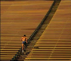 Man running empty stadium steps