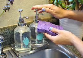 a hand pushing onto a soap dispenser next to another one with a purple dish sponge