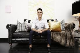 homepolish co founder noa santos sits on his vintage black leather chesterfield sofa in his black leather sofa perfect