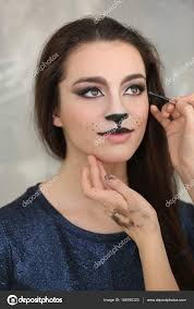 visagiste applying cat makeup onto face of beautiful young woman in salon stock photo