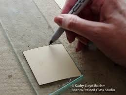below i m using a pistol grip cutter to score a line directly on top of the sharpie line cutting should be done at a 90 degree angle with moderate