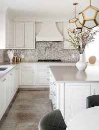beautiful off white kitchen boasts an off white island accented with satin nickel pulls and a taupe quartz countertop lit by two robert abbey pythagoras