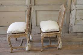 pair of pickled oak side chairs hand carved with cane back and cane seats