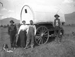 pioneer people 1800s. three men, a woman and their dog next to covered wagon in 1878. pioneer people 1800s v