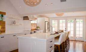 fantastic gleaming white kitchen with mosaic glass tiles backsplash viva terra lotus flower chandeliers white kitchen cabinets kitchen island with white