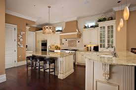 kitchen with white cabinets island and mahogany floors