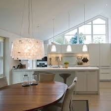 kitchen dining lighting. kitchen with neutral cabinetry island unit wood dining table and pendant lights lighting s