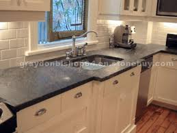 white kitchen cabinetry with soapstone countertops and a subway tile uneven countertop