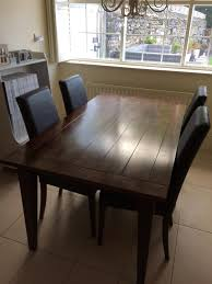 solid dark wood dining table by next with matching chairs