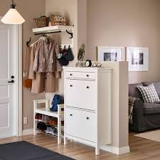 A small hallway with a white shoe cabinet and a seating bench with shelves  for shoes