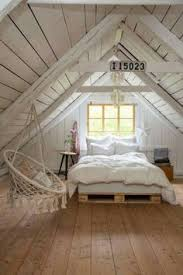 Cozy cottage style bedroom in the attic. Wide plank wood floors. White and  wood