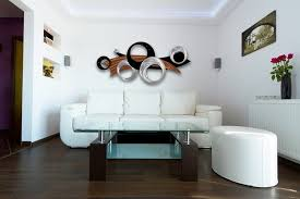 mahogany wooden floor with white leather couch and unique wall art for modern living room ideas