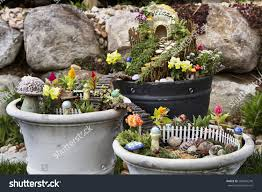 fairy garden in a flower pot with walking path wooden bridges and a fairy house