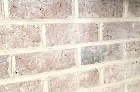 close up detail of brick wall fireplace with a diy whitewash treatment applied