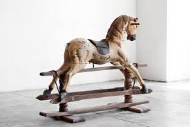 handmade wooden rocking prancing horse with leather saddle and metal spur mounted wooden trestle base