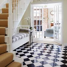 classic hallway with gloss black and white flooring upholsted wooden bench and sofa in living