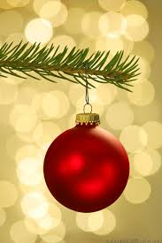A red matte christmas ornament hanging from a Christmas tree branch with a  sparkling gold background.