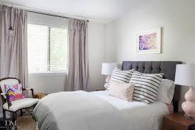 pink and gray bedroom features a gray tufted headboard on bed dressed in gray striped shams and a pink trellis pillow in kelly wearstler imperial trellis