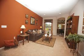 Burnt #orange accent wall perfectly pairs with the neutral furnishings and  flooring. Highland Homes