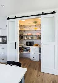 gorgeous walk in kitchen pantry behind a sliding barn door via sarahsarna