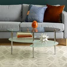 Both the rectangular coffee table and square side tables have lower shelves and feature metal x accents on two of their sides while metal brackets embrace the four top corners of each table. Walker Edison Mid Century Modern Oval Glass Coffee Table From Walker Edison Accuweather Shop