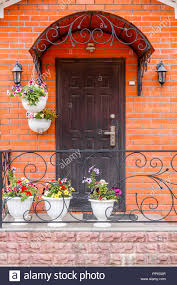 a beautiful porch in a rich house with black door red brick wall and flower pots