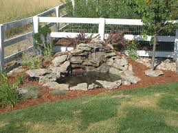 small diy ponds with waterfall and stone border in the corner backyard garden house design with wooden fence and railings ideas