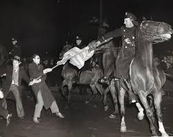 a mounted police officer attempts to take flag away from anti demonstrator outside of madison square garden february 20 1939