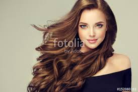 brunette with long and shiny wavy hair beautiful model with curly hairstyle