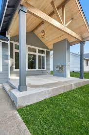 This Linear Outdoor Fireplace Features A Smooth Cement Board Siding With Metal Brackets It S Painted Gray To Enha Outdoor Fireplace Porch Beams House Exterior