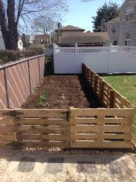 pallet fence a great inexpensive way to fence in garden and it looks nice too