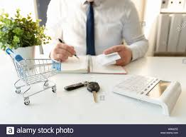 Businessman Calculating Shopping Expenses For Car Purchase